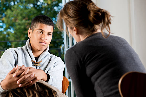 mixed race teenager  talking to counsellor or teacher - teen counseling stock photos and pictures