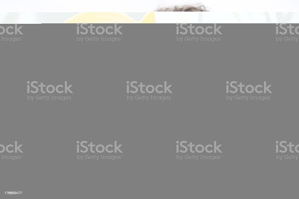 Mixed Race Toddler Girl Wearing Overalls Sitting in a Chair stock photo