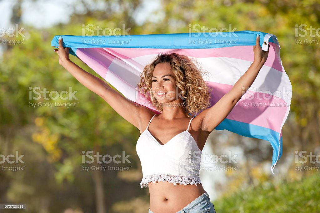 Mixed Race Transgender female with pride flag stock photo
