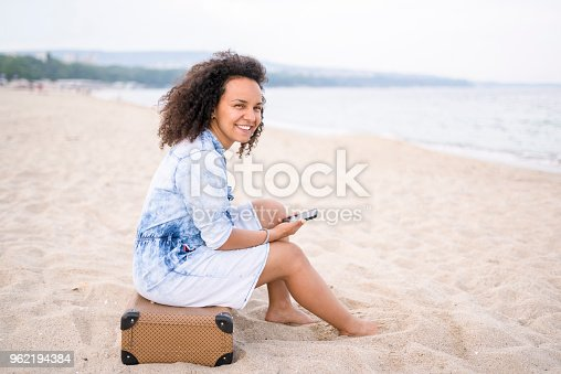 Mixed race traveler holding her smart phone. Exploring the South beach of Varna, Bulgaria on a summer day.