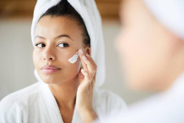 Mixed Race Woman Applying Face Cream stock photo