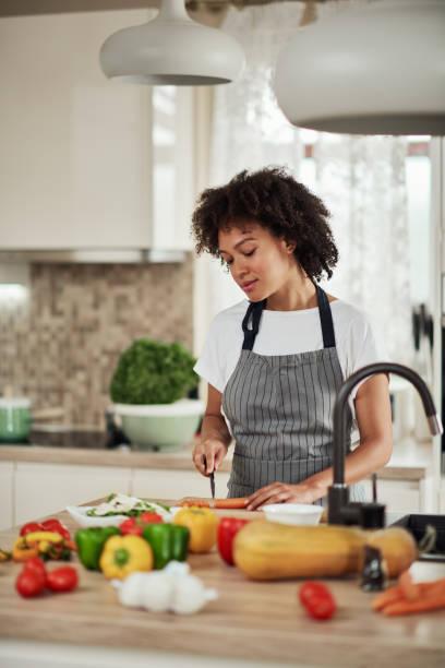 Gemischte Rasse Frau schneiden Karotten in der Küche zu Hause. – Foto