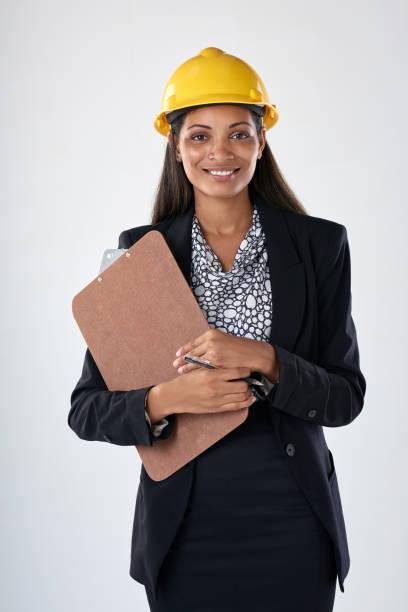 ingeniero de mujer de raza mixta usando un casco y llevando el portapapeles - arquitecta fotografías e imágenes de stock