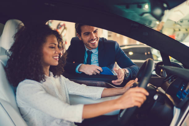 Mixed race woman enjoying new car Smiling woman in the showroom enjoying luxury car car salesperson stock pictures, royalty-free photos & images