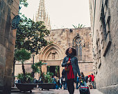 Smiling woman admiring the architecture while pulling a suitcase in Barcelona