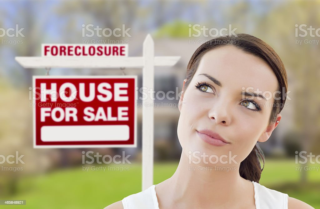 Mixed Race Woman In Front of House and Foreclosure Sign stock photo