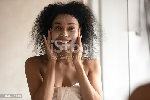 African 30s young woman after shower is wrapped in towel looking in mirror pampering herself applying face mask use anti-aging beauty product feeling happy, skin care, everyday morning routine concept