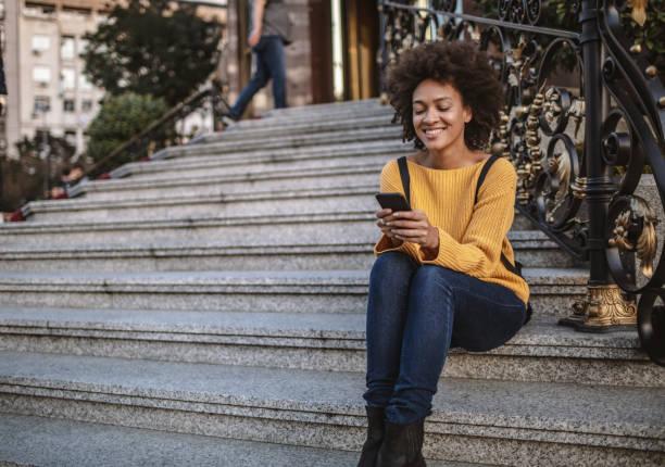 Gemischte Rasse Frau auf Stufen mit Smartphone – Foto