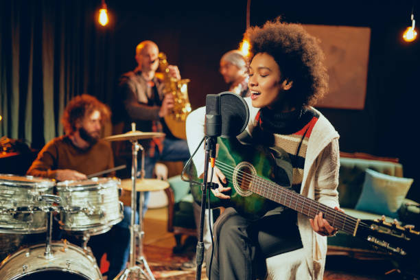 Mixed race woman singing and playing guitar. Mixed race woman singing and playing guitar while sitting on chair with legs crossed. In background drummer, saxophonist and bass guitarist. performance stock pictures, royalty-free photos & images