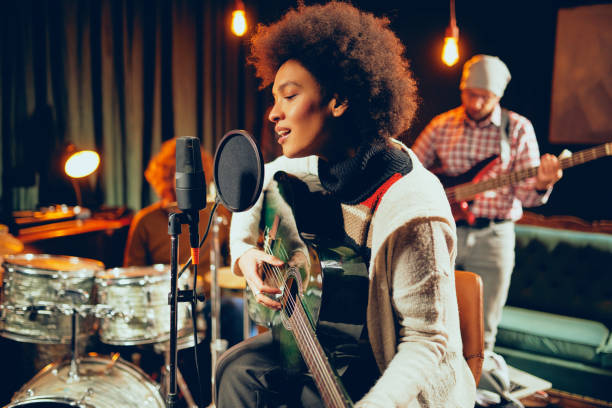 Mixed race woman singing and playing guitar. Mixed race woman singing and playing guitar while sitting on chair with legs crossed. In background drummer and bass guitarist. recording studio stock pictures, royalty-free photos & images