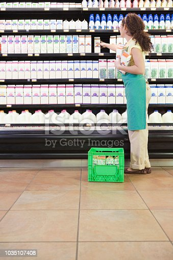 Mixed Race woman stocking shelves at grocery store