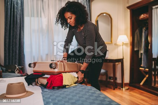 Mixed race woman unable to close suitcase before leaving the hotel room
