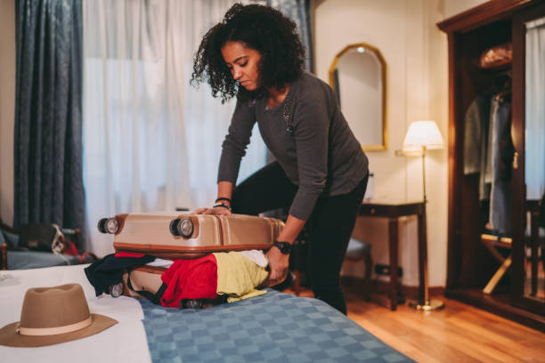 Mixed race woman struggling with overflowing suitcase before journey stock photo