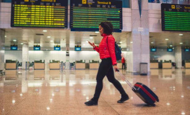 Mixed race woman texting at the airport terminal Young woman with wheeled luggage walking at the airport and texting val d'oise stock pictures, royalty-free photos & images