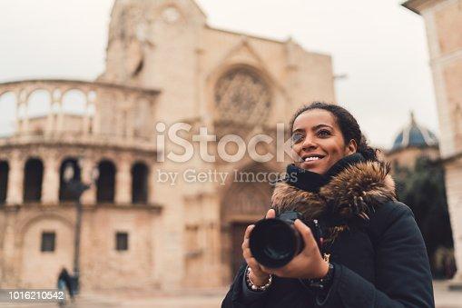 Smiling woman with camera exploring Valencia