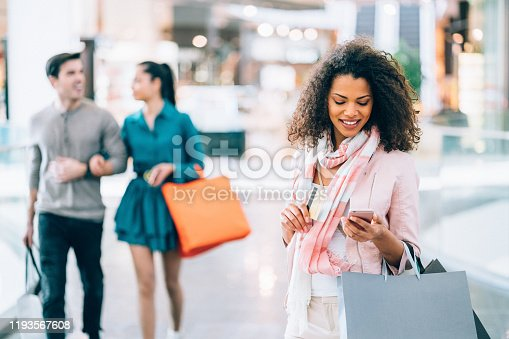 Woman on shopping checking balance of her credit card on smartphone mobile app
