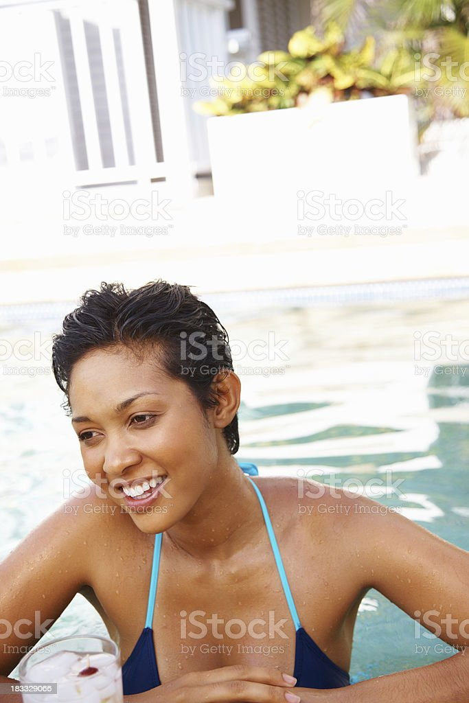 952e23564c6 Mixed race woman wearing bikini enjoying in swimming pool - Stock image .