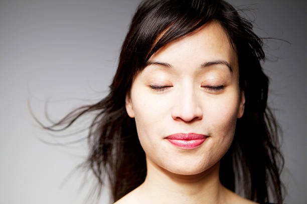 Mixed Race Woman with Eyes Closed and Smiling Happy young woman in her 30s, Asian and Latina mixed race, is facing front with her eyes closed and smiling. blinking stock pictures, royalty-free photos & images