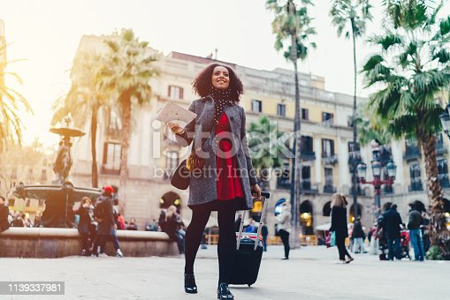 Young businesswoman in Barcelona using a map for navigation in the city