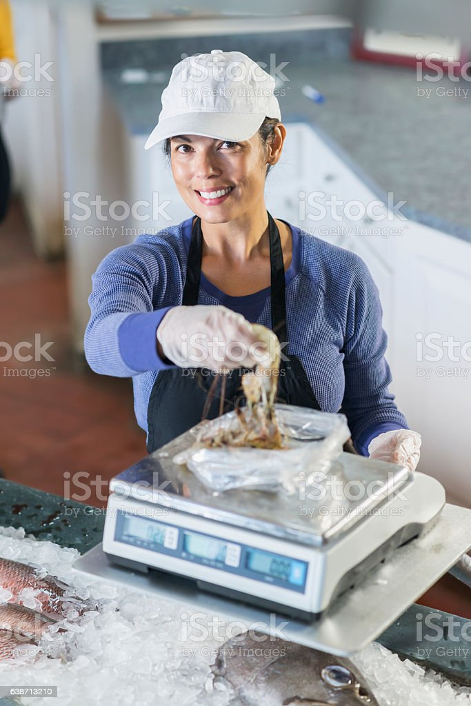 Mixed race woman working in fish market, weighing shrimp stock photo