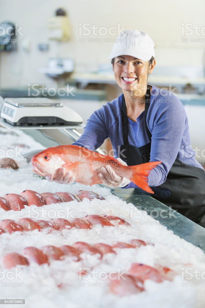 Mixed race woman working in seafood market holding fish stock photo
