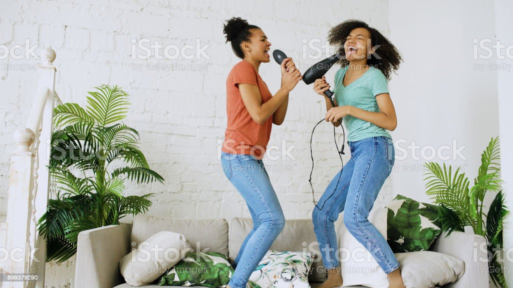 Mixed race young funny girls dance singing with hairdryer and comb jumping on sofa. Sisters having fun leisure in living room at home concept royalty-free stock photo