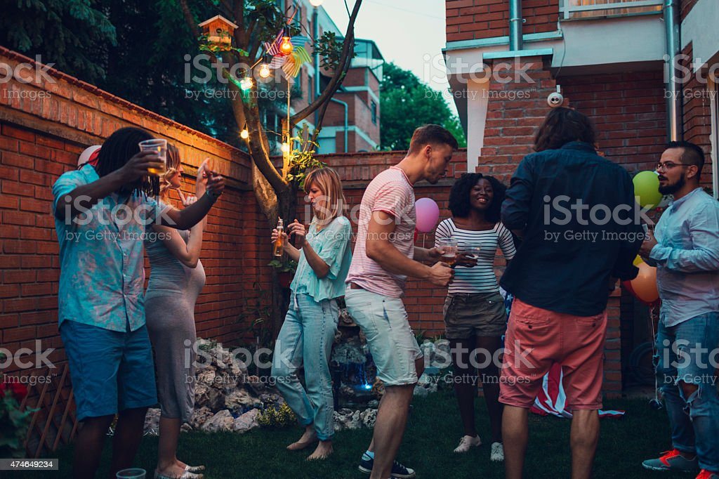 Mixed Race Young Happy People Dancing At Backyard Party. stock photo