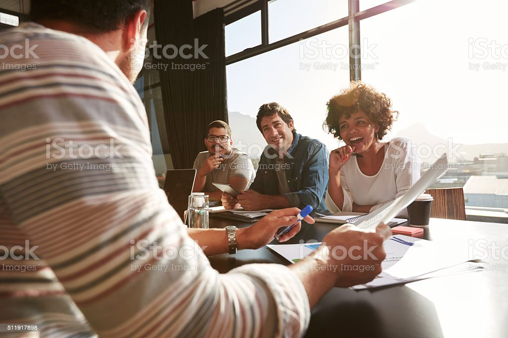 Mixed race young people discussing new and creative business ideas stock photo