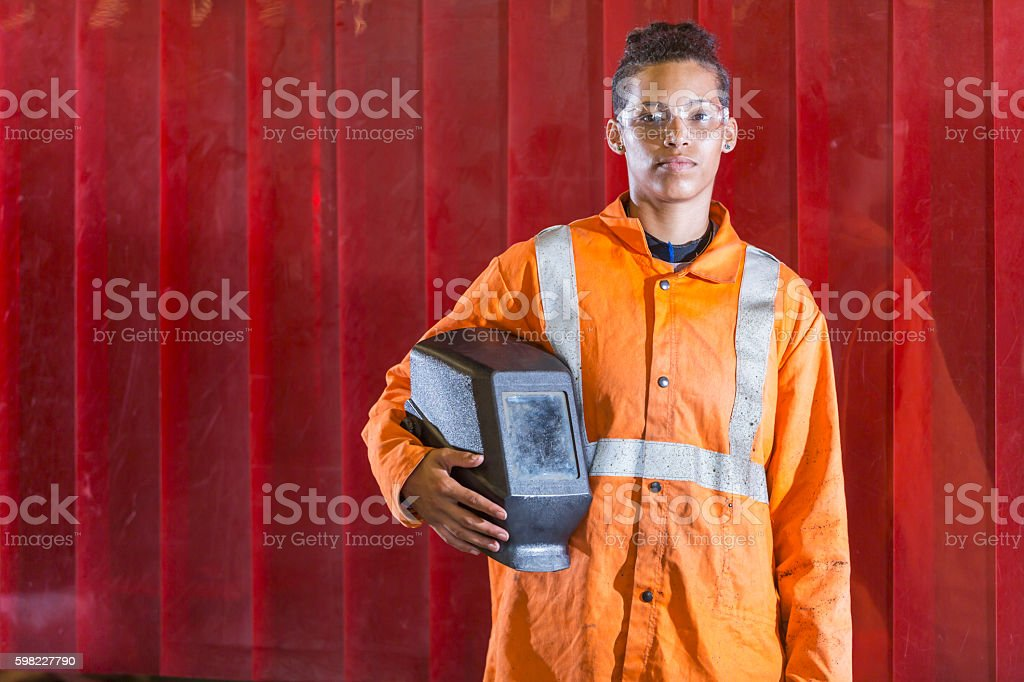 Mixed race young woman holding welding mask stock photo