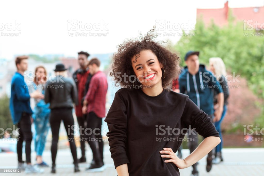 Mixed race young woman smiling, outdoor portrait Outdoor portrait of afro young beautiful woman smiling at camera. Group of her friends in the background. 20-29 Years Stock Photo
