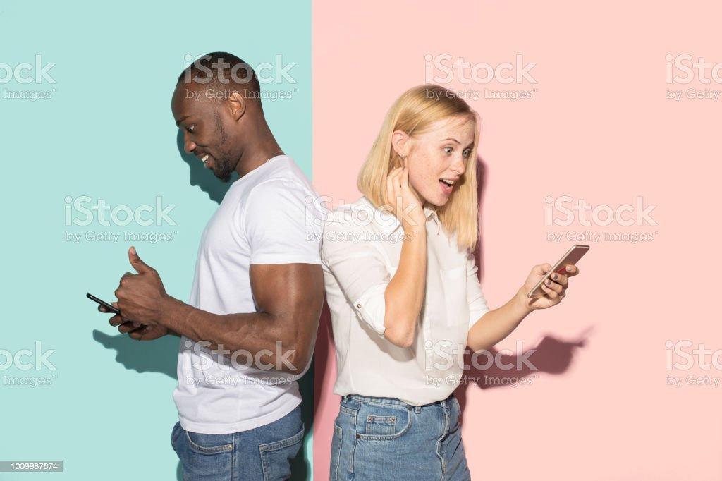 Par corrió mixto de estudiantes móviles. Caucásica chica y su novio africano posando en el estudio foto de stock libre de derechos
