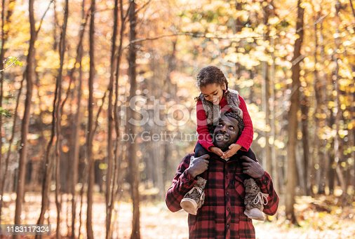 Mixed race family doing piggyback, in the forest, during autumn, Quebec, Canada