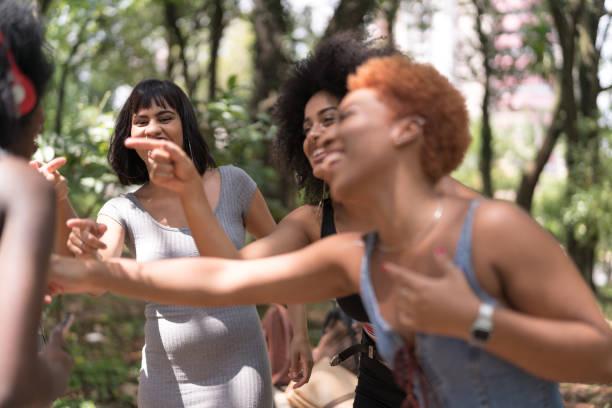 gemischten rassischen gruppe tanzen im park - bands der 90er stock-fotos und bilder