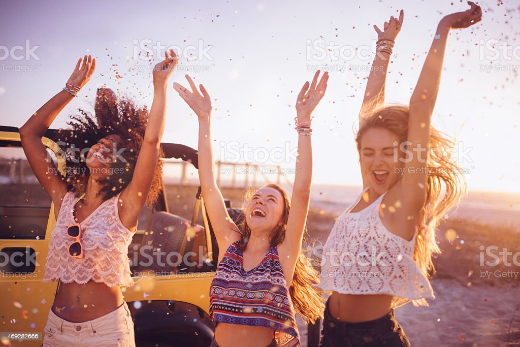 Mixed racial group dancing on a beach with confetti stock photo