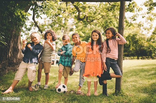 Girls and boys of mixed racial groups standing in a row smiling at the camera with a soccer ball in a lush green park with trees and grass on a summer day