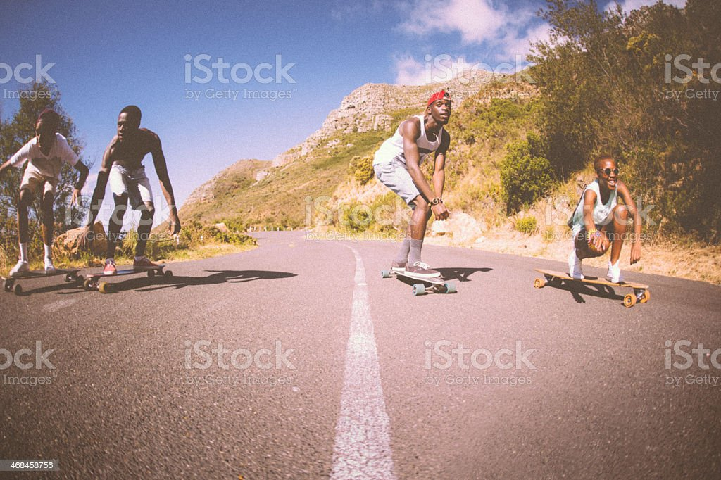 Mixed racial group of teen skateboarders racing downhill together stock photo