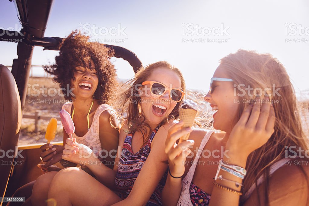 Mixed racial group of teens laughing with ice creams stock photo