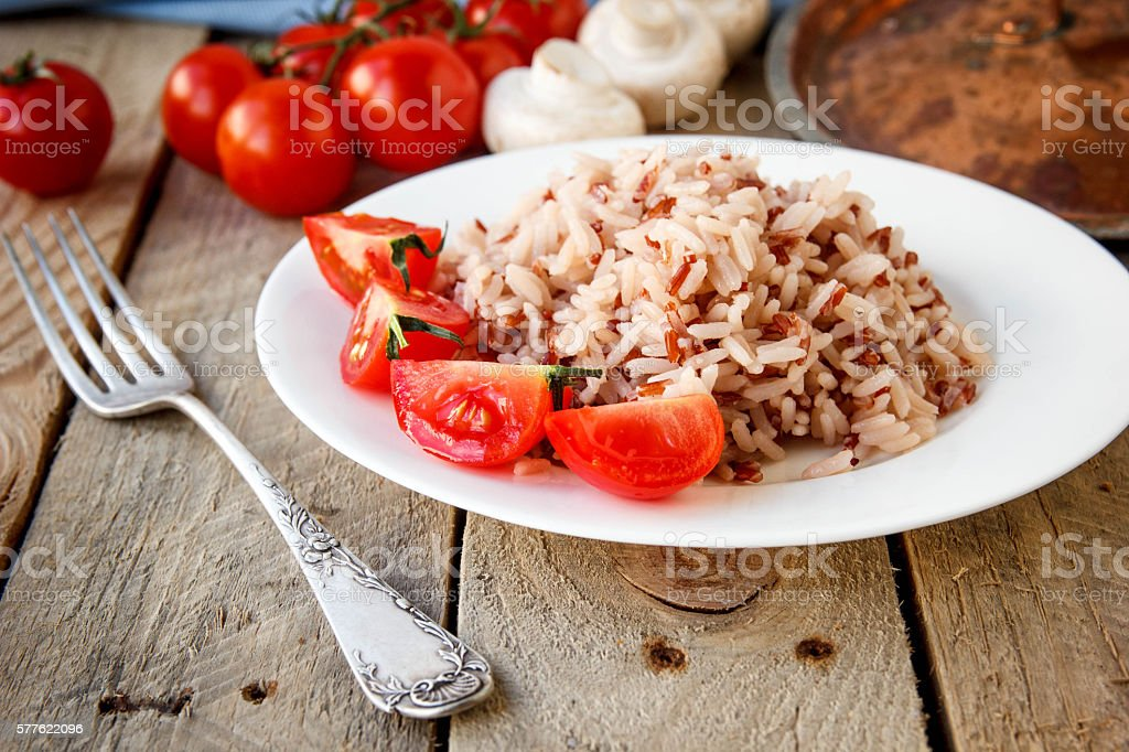 Mixed rice with tomatoes and mushrooms. stock photo