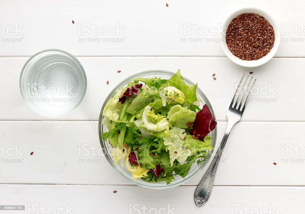 Mixed salad in glass bowl with flax seed and water on white wooden table. stock photo