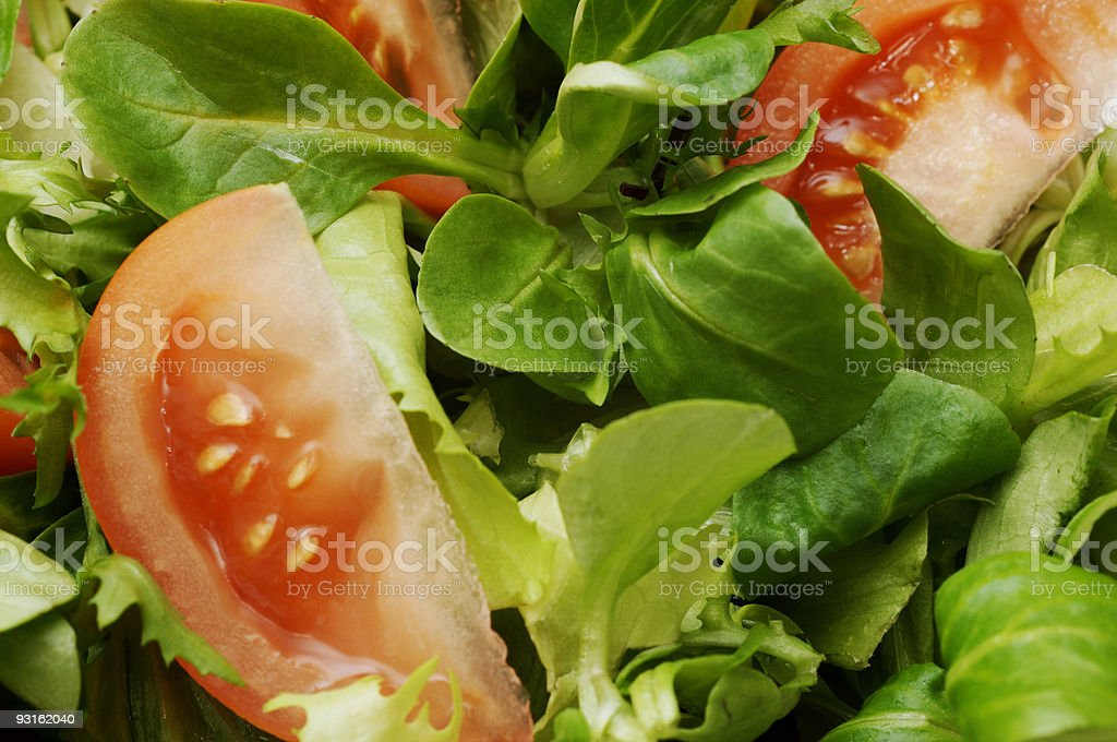 Mixed salad leaves background with sliced tomato royalty-free stock photo