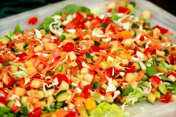 Mixed salad of fruits and vegetables and various flavors: fresh tomatoes, cucumbers, cabbage, green salad, apple, carrots, pear, pineapple, pepper, orange. Food nutrition for turtle at home and zoo. stock photo