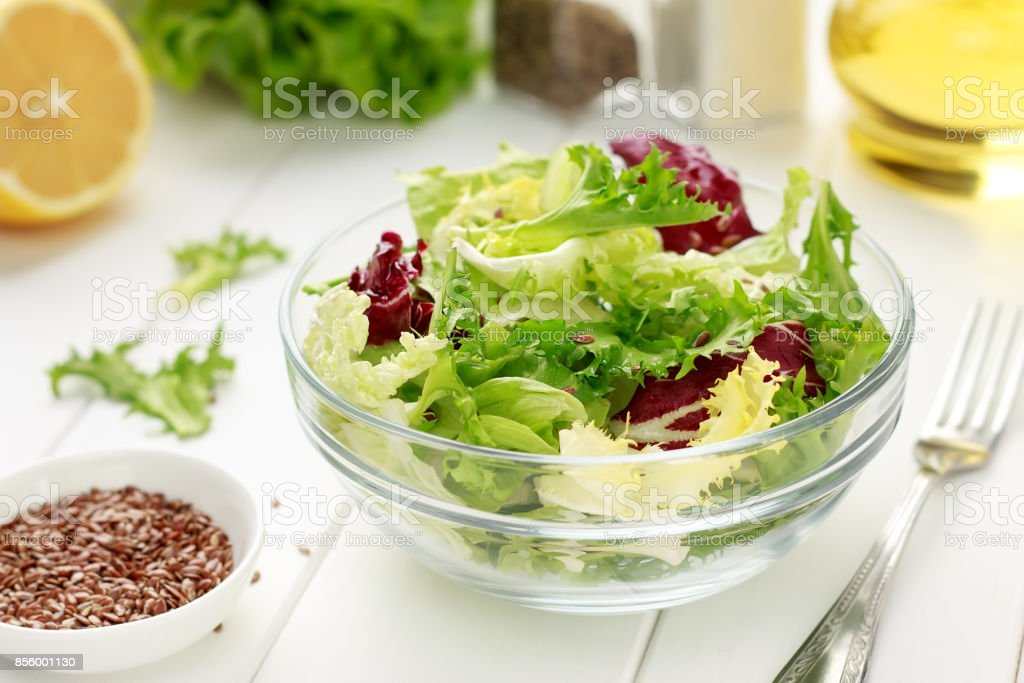 Mixed salad of iceberg, radiccio, endive, cabbage with flax seeds, oil and lemon on white wooden background. stock photo