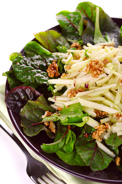 Mixed salad with kohlrabi, apples and walnuts on white isolated stock photo