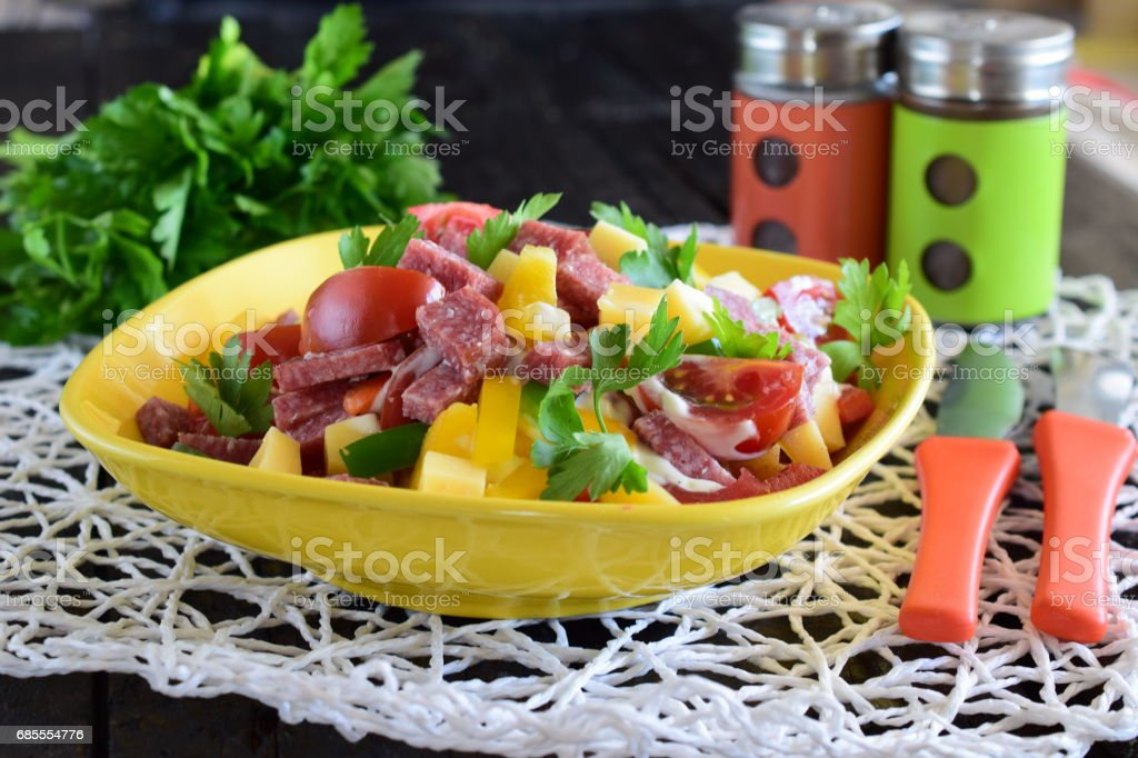 Mixed salad with salami sausage, cheese, tomato, and paprika with yogurt and garlic sause in a yellow ceramic bowl. Easy cooking 免版稅 stock photo