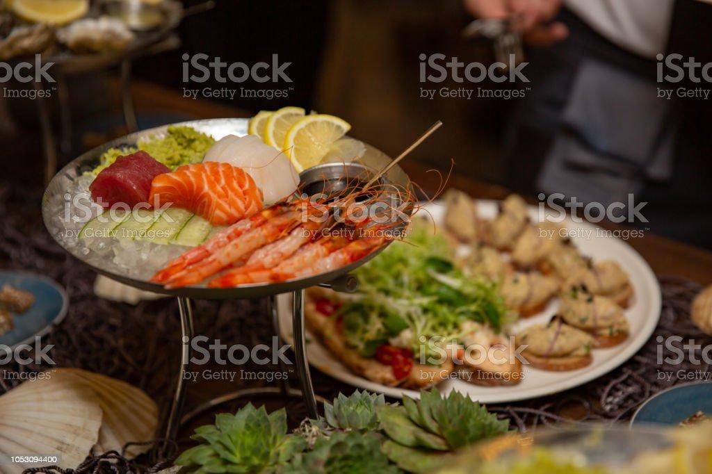 Mixed Sliced Fish Sashimi And Shrimps On Ice In Black Bowl Sashimi