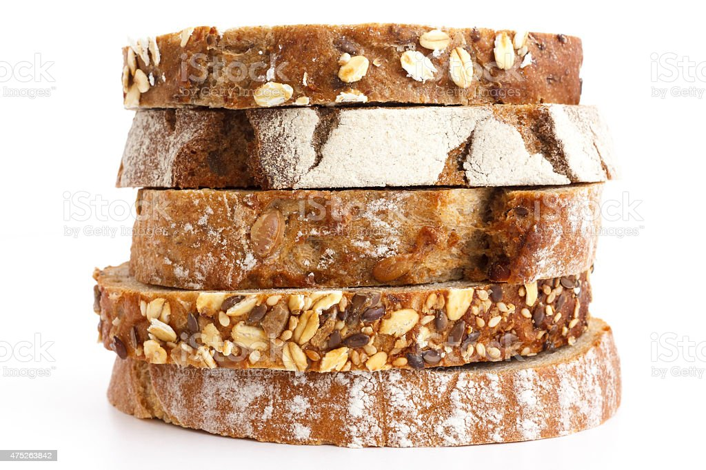 Mixed slices of health breads stacked. White surface. stock photo