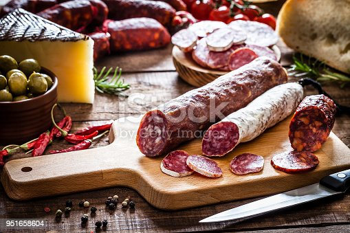 Mixed spanish chorizo pieces on a cutting board shot on rustic wooden table. Some chorizo slices are on the board. A plate with sliced chorizo is out of focus on background. A brown bowl with green olives, a piece of cheese and a loaf of bread complete the composition. A kitchen knife is in front of the cutting board. Predominant colors are red and brown. Low key DSRL studio photo taken with Canon EOS 5D Mk II and Canon EF 100mm f/2.8L Macro IS USM