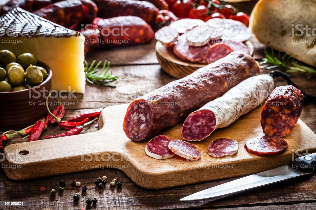 Mixed spanish chorizo pieces on rustic wooden table stock photo