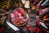 Mixed spanish chorizo slices plate on rustic wooden table