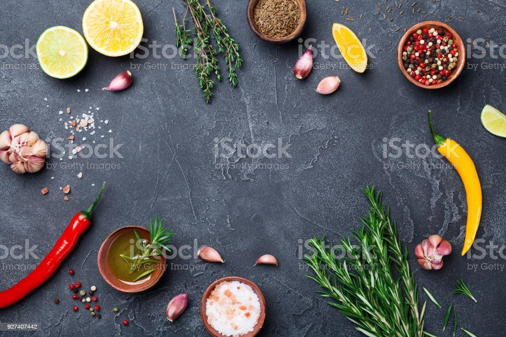 Mixed spices and herbs on black stone table top view. Ingredients for cooking. Food background. stock photo